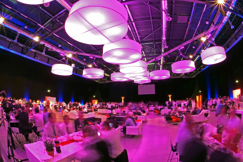 a large corporate event lighted up with purple tint, people sitting at tables